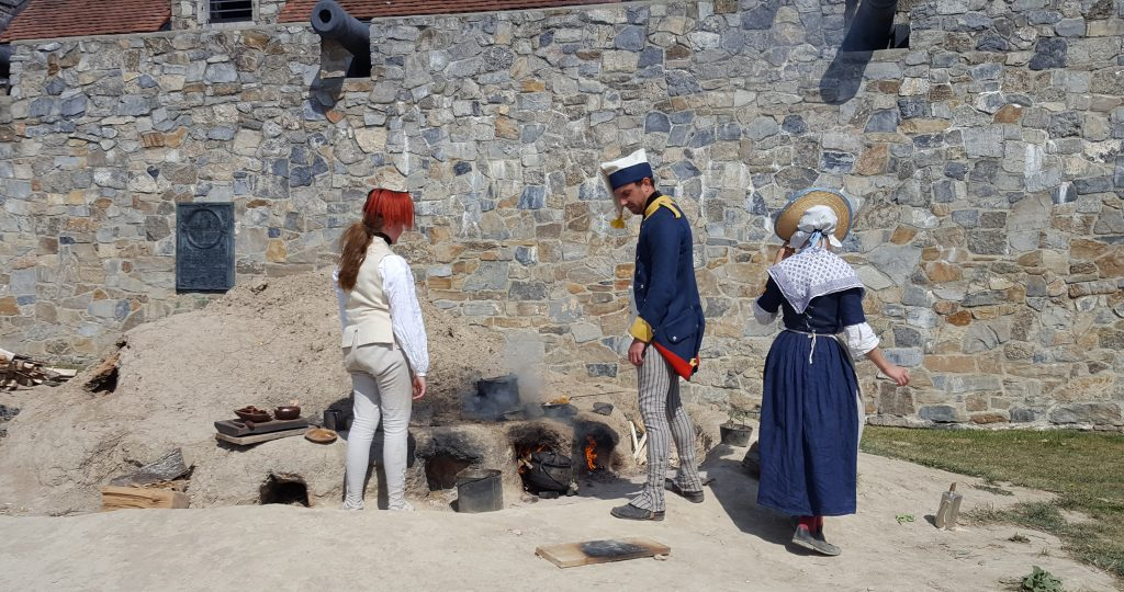 Living Museum actors explain cooking in this oven made from a pile of dirt at Fort Ticonderoga.