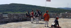 Fort Ticonderoga firing cannon at mountain top enemy.